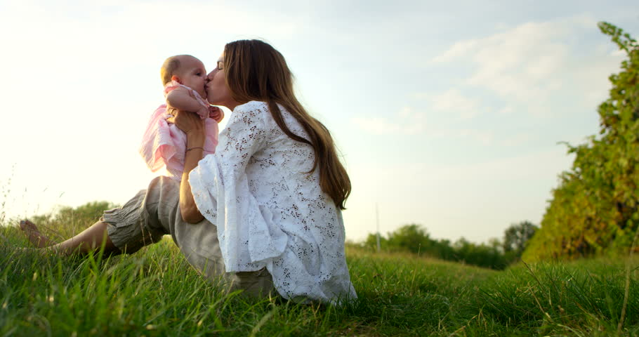Super slow motion of young caucasian mother playing with her baby girl and enjoying their happy moments together in a meadow of vineyard on a sunshine in 4k  | Shutterstock HD Video #11958719