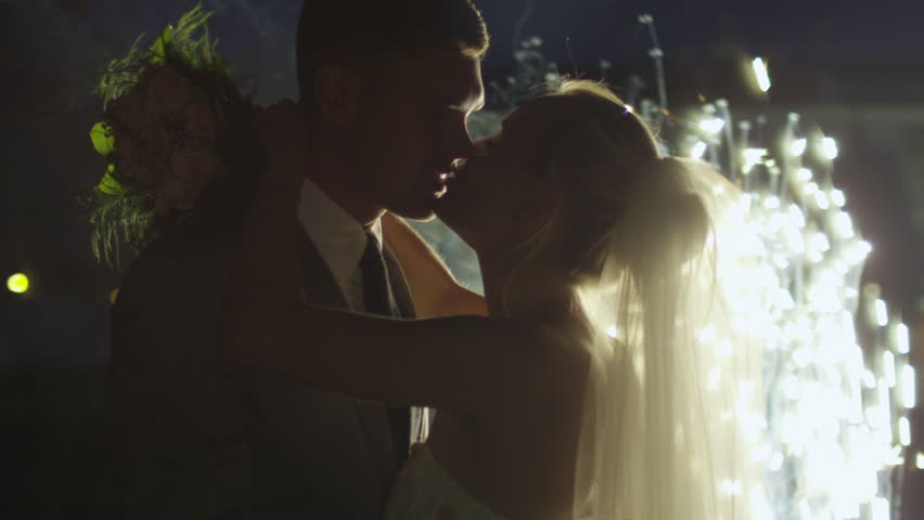 Happy young newlyweds are kissing next to fireworks in a park in the evening. Shot on RED Cinema Camera in 4K (UHD).