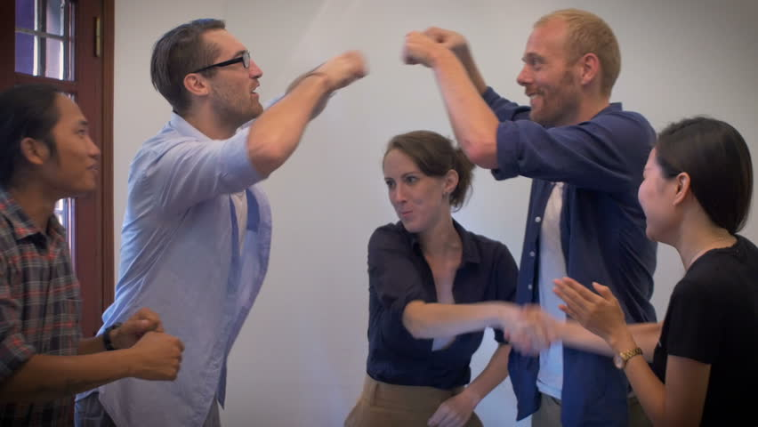 A mixed race group of young workers high five and fist bump each other to celebrate their success on their collaboration and creative work in a casual work environment.