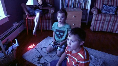 Two Twin Brothers sit in front of a television playing video games