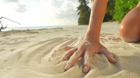 SLOW MOTION CLOSE UP: Playing with beautiful white sand at exotic beach
