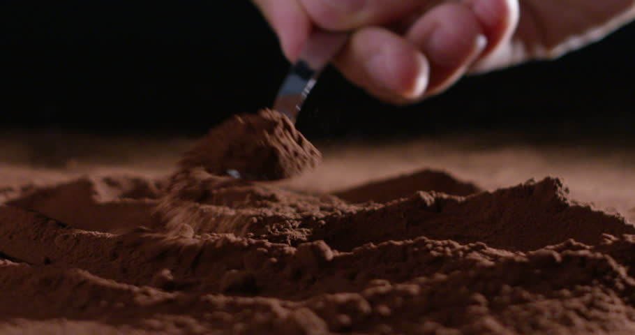 Super slow motion of cocoa powder dosage with a small spoon isolated on a black background in 4k ( macro close up)