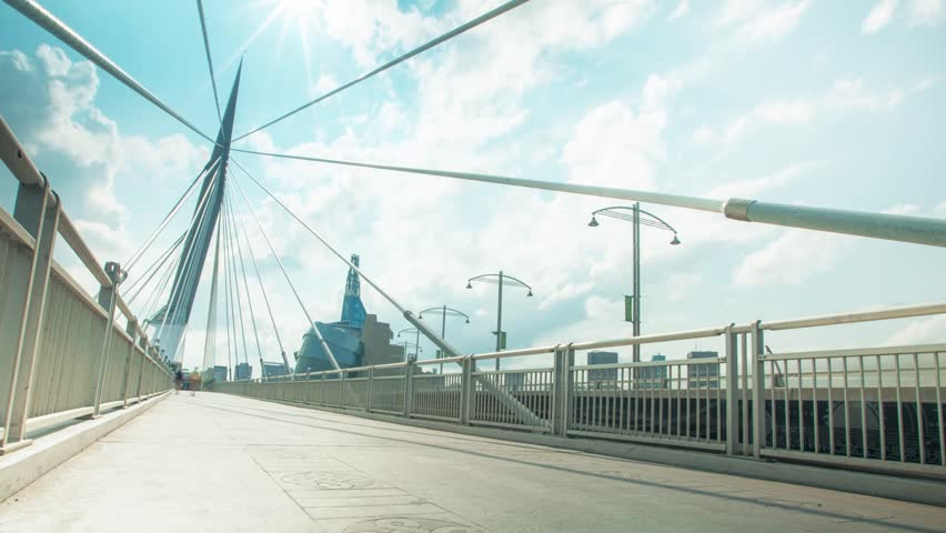 Version 2 of Beautiful Winnipeg Time lapse of pedestrians passing over the iconic Provencher Bridge with the Human Rights Museum in the background on Sunny Day.