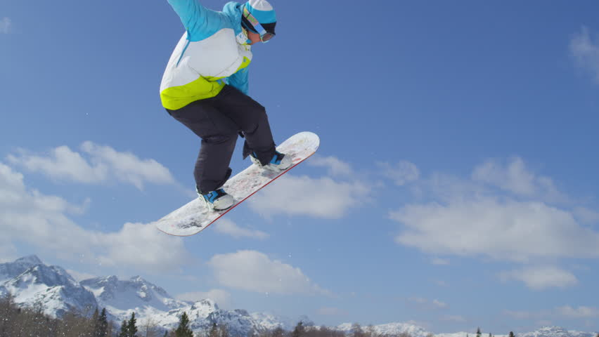 SLOW MOTION CLOSE UP: Snowboarder jumping the kicker on a beautiful sunny winter day in snow park