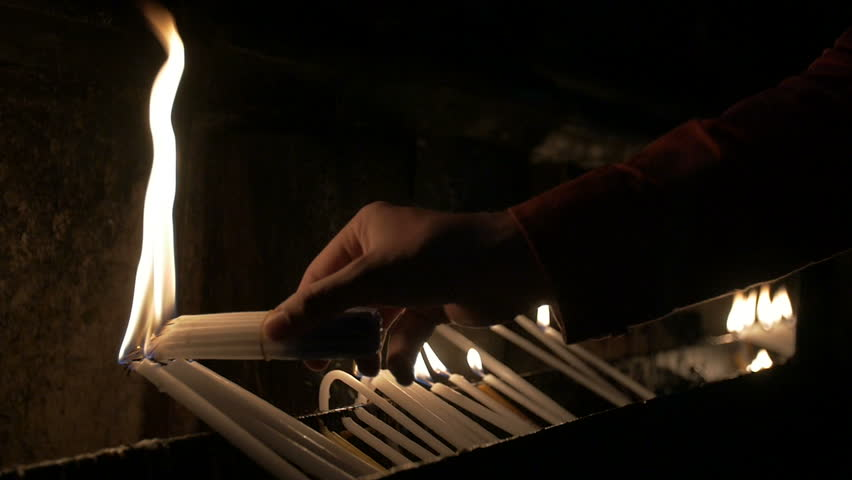 Christian pilgrim light candles near the Altar of the Crucifixion in the Church of the Holy Sepulchre during visit to the Holyland  in Old City Jerusalem, Israel.