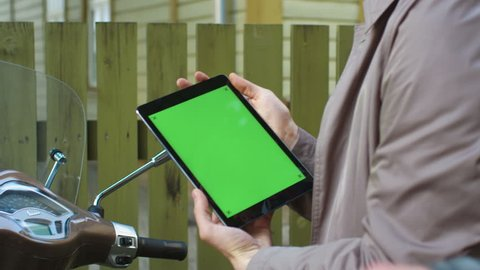 Young man in an elegant beige trench coat sits on a scooter and holds a tablet with green screen. Shot on RED Cinema Camera in 4K (UHD).
