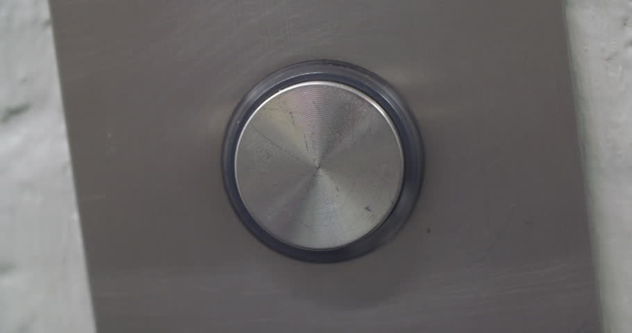 Man's finger reaches in and presses elevator button which lights up.  Angled view, tight from front, macro.  Originally recorded in 4K.
