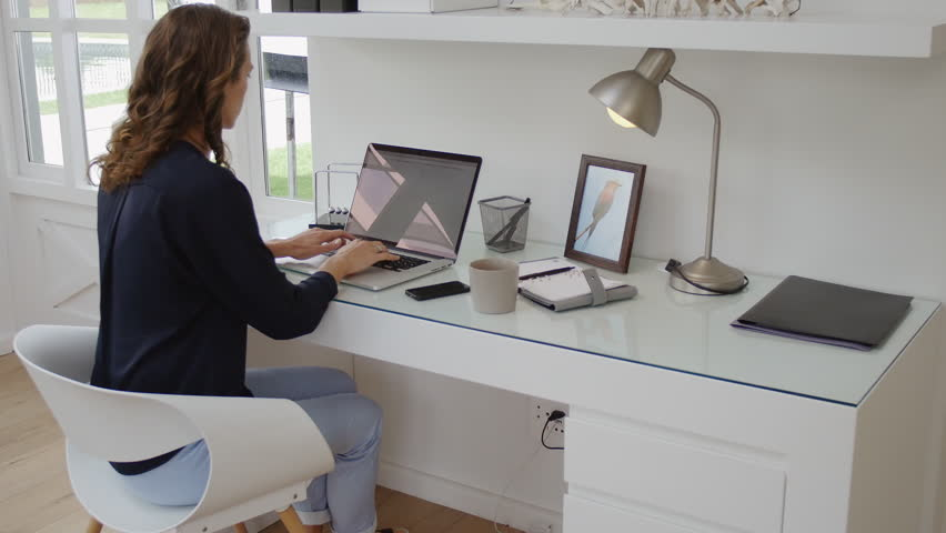 successful woman working in modern home office with laptop