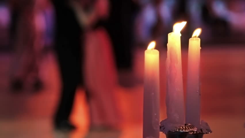Dancing couples, burning candle and beautiful flowers. Traditional Vienna ball.