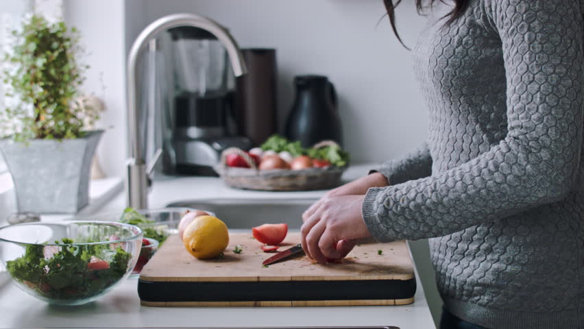 Woman hands preparing a home made salad and squeezes lemon juice