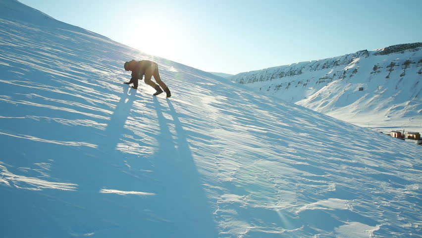 A man trying to climb the mountain on a slippery frozen snow, slips and falls. Time lapse.