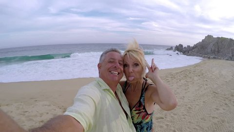 An older couple having fun and taking selfies on the beach