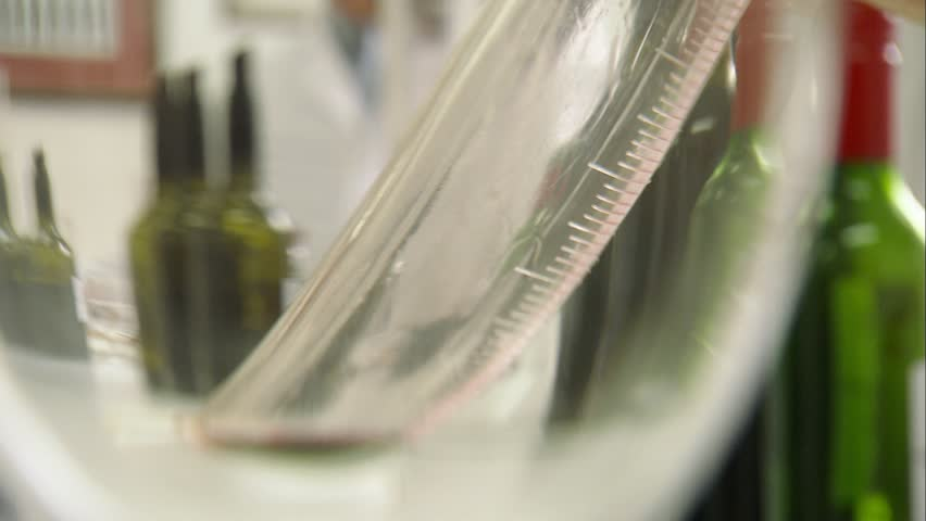 Footage of winemakers laboratory testing wines in winery lab. Measurement alcohol content cold stability density malic acid red grape color sugar sulfur dioxide pH of grapes acidity chemistry in wine