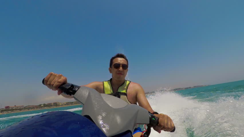 Front POV (point of view) view of Asian male adult riding jet ski on sea and turning left hard