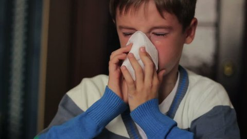 Sick boy blowing his nose into a napkin while sitting at a table at home