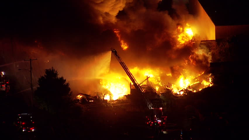 Night time aerial shot of a large building or warehouse fire. Fire department and emergency crews on scene to fight and extinguish the flames before the building is destroyed. NX
