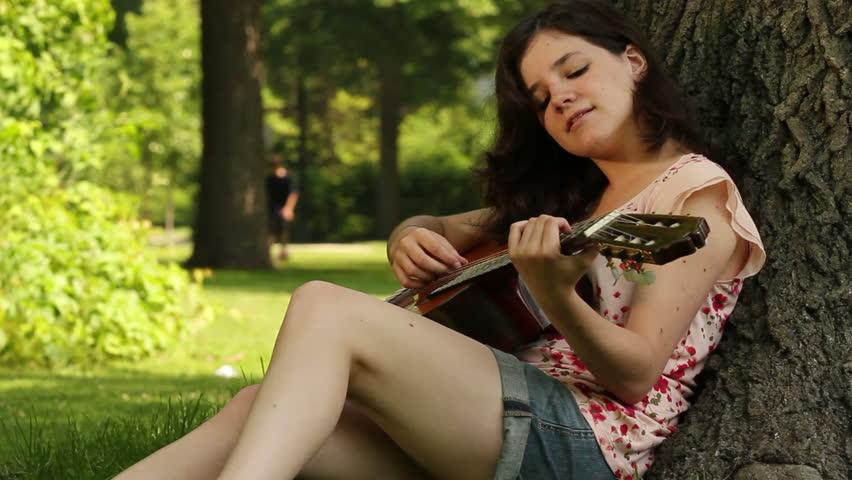 Teenager plays guitar in park.