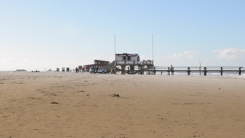 St. Peter Ording, September 27, 2015 - The famous and Germany's longest sand beach in St. Peter Ording. Tourists walk on the beach. A beach bar is located at the edge of the shore.  | Shutterstock HD Video #12236234