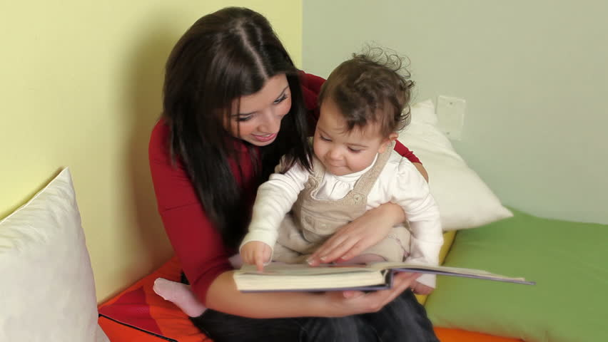 Baby girls listening to fairy tale in kindergarten and educator reading book