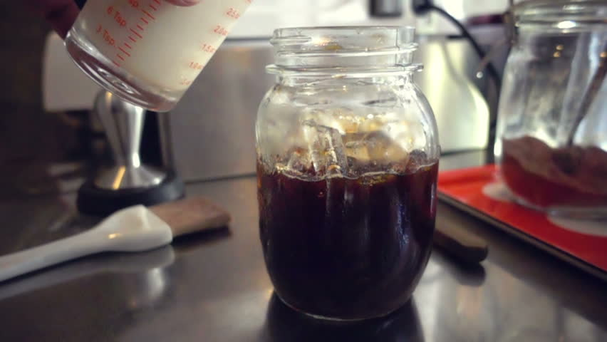 Barista mixing a cup of milk into fresh coffee, slow motion