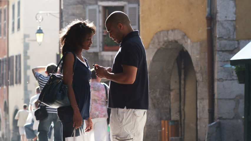 Annecy-France - 06,30,2005: couple standing on a European street using a cell phone for directions   Shutterstock HD Video #12252629