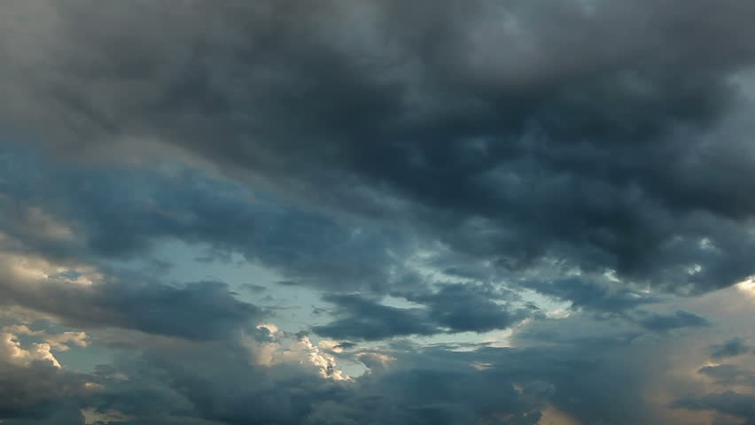 Clouds running across the rapidly darkening sky at sunset. Timelaps