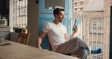 Good looking man at home drinking coffee using digital tablet happy loft apartment in pajamas