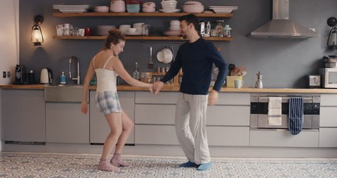 Morning at home happy young couple newly wed dancing listening to music in kitchen wearing pajamas in love having fun