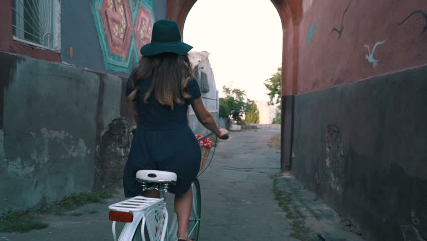 young woman riding on old vintage bike in city