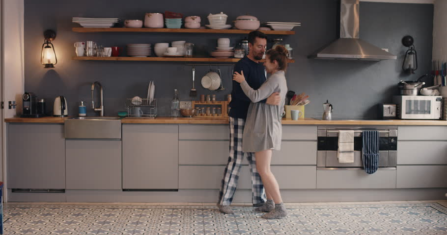 Happy young couple newly wed dancing listening to music in kitchen wearing pajamas coffee morning at home in love having fun | Shutterstock HD Video #12273491