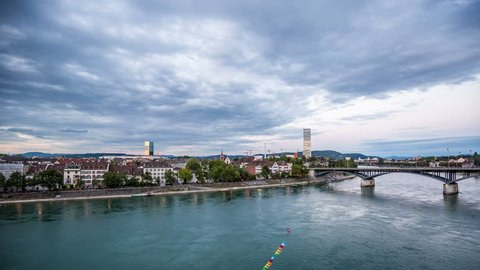 BASEL, SWITZERLAND – August 20, 2015: Basel skyline with, river, waterfront, sky with clouds in the evening timelapse, pan shot City skyline in the evening, day to night timelapse