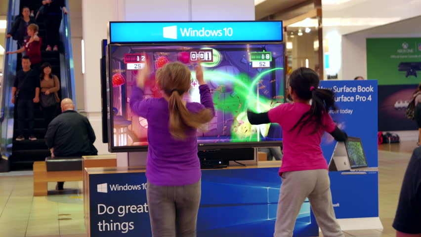Burnaby, BC, Canada - October 16, 2015 : Children dancing with Microsoft demonstrated game beside Window store