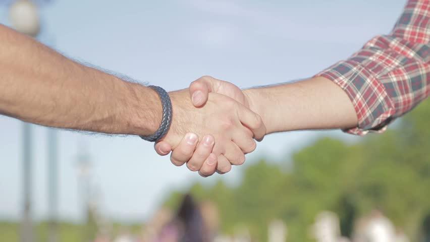 Friendly handshake. Friends handshaking of two hands outside. Meeting of two friends on the street. | Shutterstock HD Video #12284429