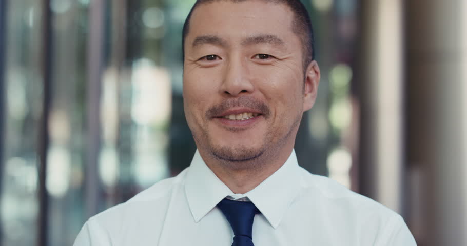 Portrait of Japanese Businessman smiling outside corporate office building real natural smile appearing confident
