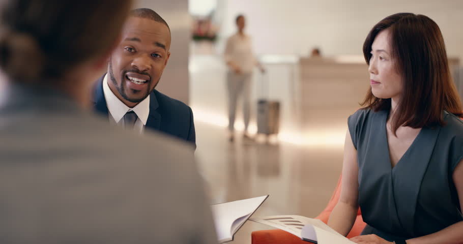 Multi-Ethnic Business people meeting in business lobby having informal group discussion
