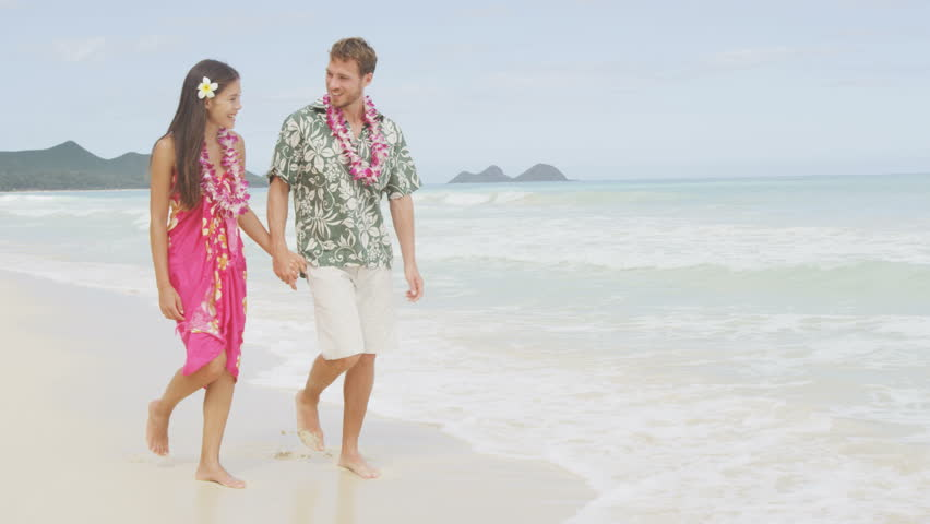 9a34d819f11 Happy couple on Hawaii vacation walking on beach with Hawaiian leis and  Aloha clothing. Caucasian man wearing typical Hawaiian shirt and Asian  woman ...