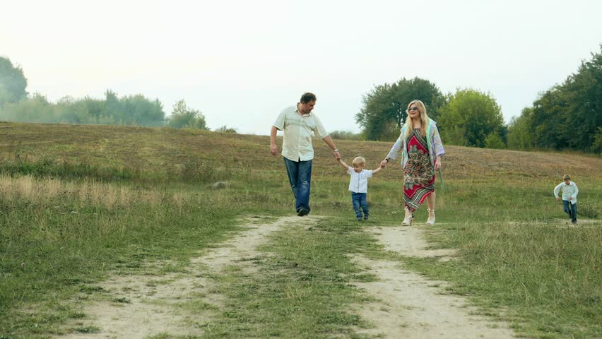 Happy cheerful full family, Caucasian parents and two children boys walking  in countryside, non-urban Holiday | Shutterstock HD Video #12384074