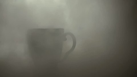 Morning with tea or coffe in cup on table with smoke mist