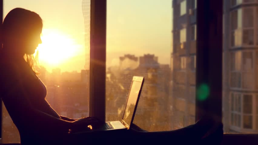 Beautiful young brunette business woman working on her laptop. Heaven sunset glass background behind her. Girl sitting on the window on modern building blurred background in city