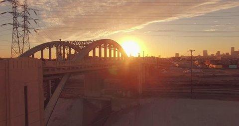 Sun peeking through iconic 6th Street Bridge arches at sunset. Los Angeles, California. Aerial view, 4K UHD.