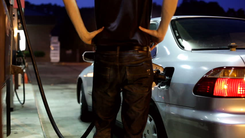 Man finishing pumping gas and getting in car
