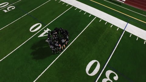 The camera spins from above as a football team in a huddle gets hyped before a game