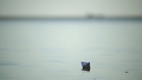 Butterfly sits on a paper boat. Paper boat on the background of a large ship  tanker on the river or sea.