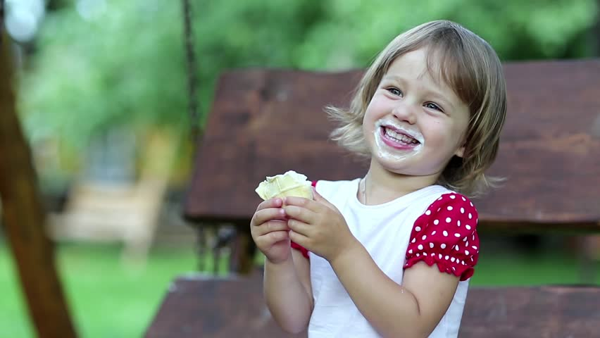 Little girl sits on the swing bench eats ice cream smiles and laughs