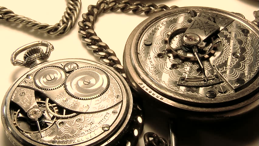 Two old pocket watches with backs off and balance wheels spinning on white counter with chains.