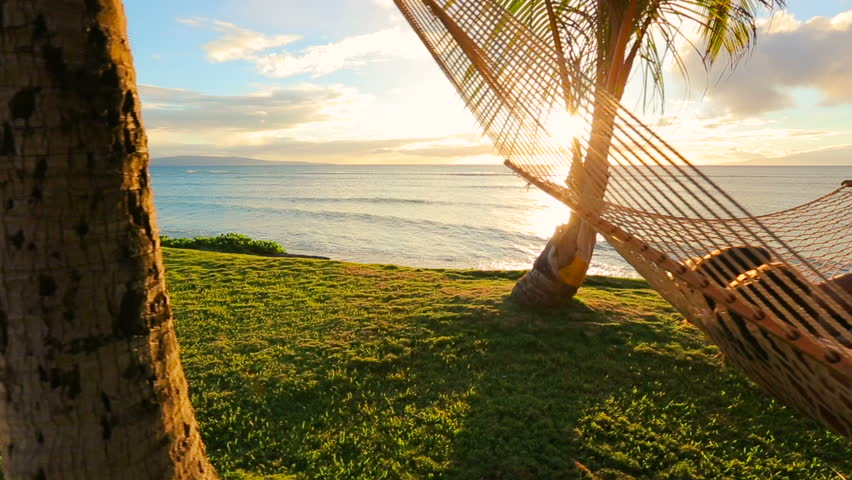 Romantic couple relaxing in tropical hammock at sunset. Summer Luxury Vacation