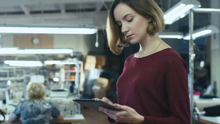 Young woman is standing in a clothing factory and using a tablet while employees work in the background. Shot on RED Cinema Camera in 4K (UHD)