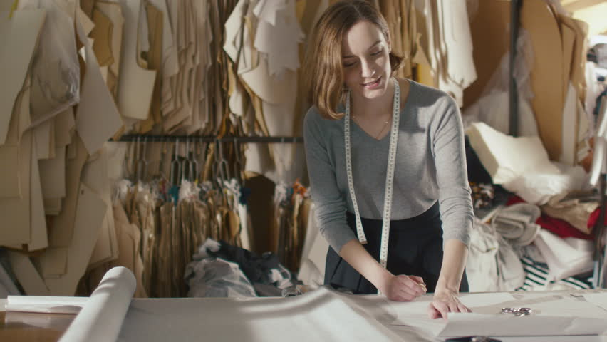 Clothing designer is working with measurements on a studio table. Shot on RED Cinema Camera in 4K (UHD).