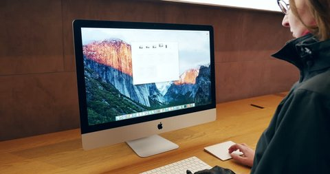 PARIS, FRANCE - OCTOBER 2015: Woman looking at the specifications and testing the new iMac 21,5 4k Retina display in Apple Store with the new Apple Keyboard and Apple Touch pad