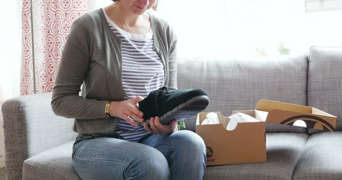 PARIS, FRANCE - Woman unboxing a freshly received box of shoes bought from Crocs online fashion store - by mistake the shoes are for men's